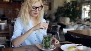 Girl With Glasses Drinking Herb Tea in a Cafe