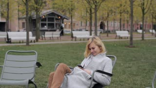 Girl With the Phone Sitting on a Chair in the Park