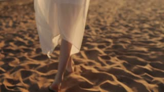 Happy Girl in a White Dress Walks on the Beach