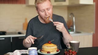 Man Eat Pancakes and Drink Tea in the Kitchen