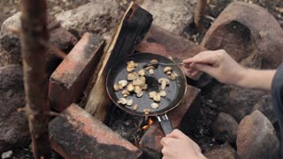 Man Fry Mushrooms on a Fire