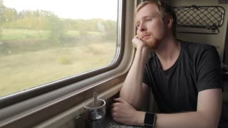 Man Looking Out the Window While Sitting in the Train and Falls Asleep
