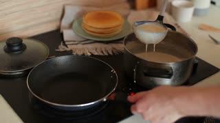 Man Prepares Pancakes in the Kitchen