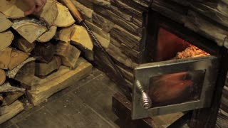 Man Throws Wood Into Fireplace
