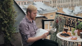 Man With Cup of Coffee Reading a Newspaper on the Balcony Overlooking the City