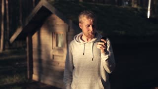 Man With the Phone Next to a Wooden House in the Woods