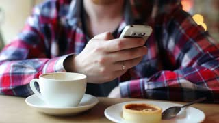 Man Writes a Message on the Phone in a Cafe