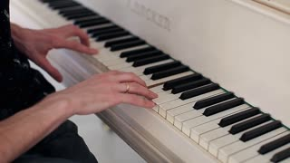 Man's Hands Playing on a White Piano