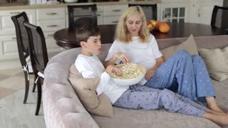 Mother and Son Are Sitting on the Couch Watching Television With Popcorn