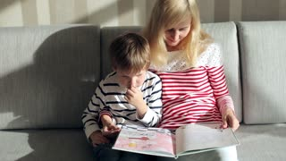 Mother and Son Reading a Book Sitting on the Couch