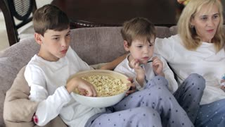 Mother and Sons Are Sitting on the Couch Watching Television With Popcorn