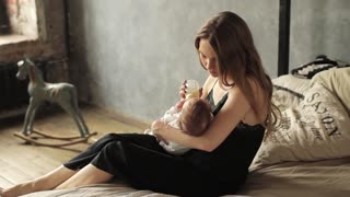 Pretty Young Woman Feeding the Baby From a Bottle, Sitting on the Bed
