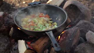 Vegetarian Stew Prepared on a Large Frying Pan Over a Fire