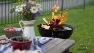 a covered table and a burning outdoor grill