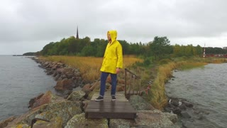 a fisherman in a yellow raincoat is standing on a stony bank