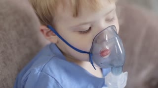 a Little Boy Breathes Through an Inhaler