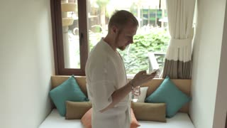 a man in a bathrobe with a phone drinking water