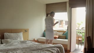 a man in a bathrobe with a smartphone in the hotel room
