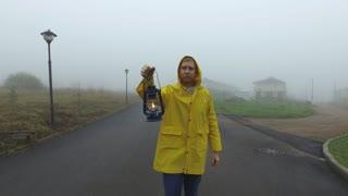 a man in a yellow cloak is walking along a foggy road