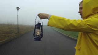 a man in a yellow cloak with a lantern walking down the road into the fog