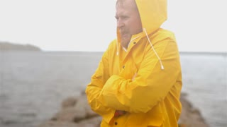 a man in a yellow raincoat is freezing, sick at the dock