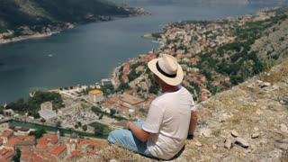 a man sitting on a cliff overlooking the city by the lake montenegro