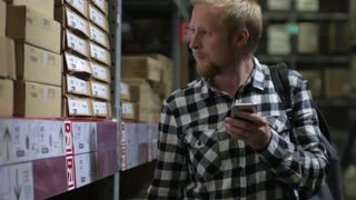 a man with a phone shopping at a warehouse store