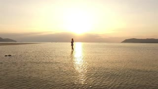 a woman is standing on the water at sunset