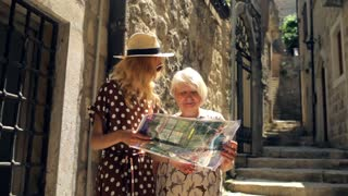 adult mother and daughter with a map on the street of the old tourist town