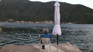 an elderly man is sitting on a chair by the lake