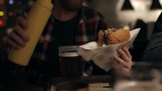Bearded Man Eating a Big Burger With Sauce in a Bar