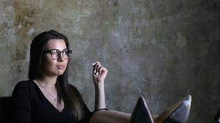 beautiful business woman with glasses resting her legs on the table