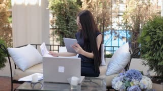 Beautiful Business Woman Working With Documents on Laptop Sitting on Terrace Coworking Center