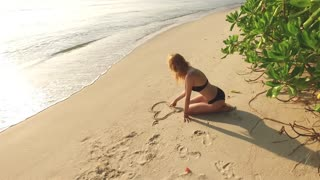 beautiful girl draws a heart in the sand on the beach