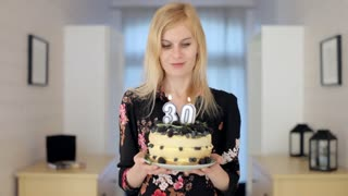 beautiful girl holding a cake with candles for 30 years and blowing them out