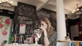 Beautiful Girl in a Cafe Drinks a Milk Cocktail