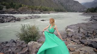 beautiful girl in a green dress on the bank of a mountain river