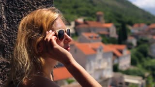 beautiful girl looks at the city in the mountains