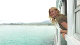 beautiful girl looks out the ship window at the sea and islands