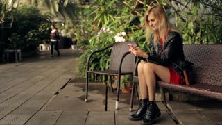 beautiful girl with a phone sits in a greenhouse