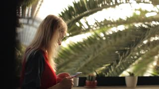 beautiful girl with phone and coffee in the greenhouse cafe