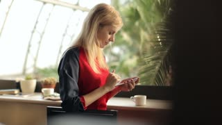 beautiful girl with phone in the greenhouse cafe