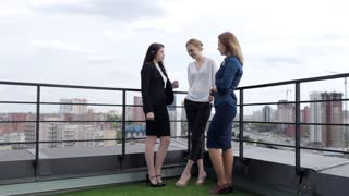 Beautiful Girls Communicate in Break at Work. Three Business Women Discuss Working on the Roof Overlooking the City