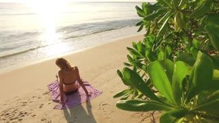 beautiful slender girl sunbathing on the beach in the tropics