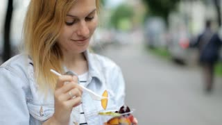 Beautiful Woman Eating Fruit Snack in Outdoors. Young Female Eating Healthy Food During Lunch Break