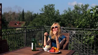 beautiful woman eating fruits on the terrace