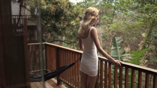 beautiful woman in a dress standing on a terrace in the jungle