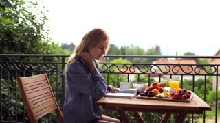 beautiful woman reading a book at breakfast on the terrace