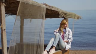 beautiful woman sits in an old boat on the lake shore