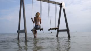 beautiful woman swinging on water swing